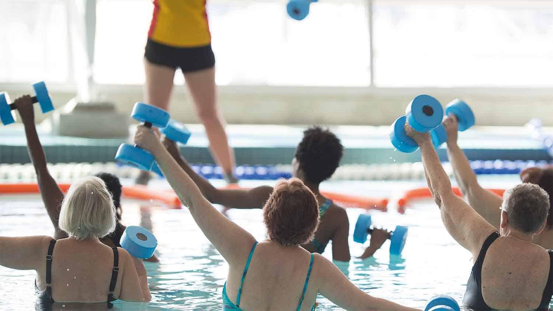 Aqua-aerobics - women in a pool waving light weights