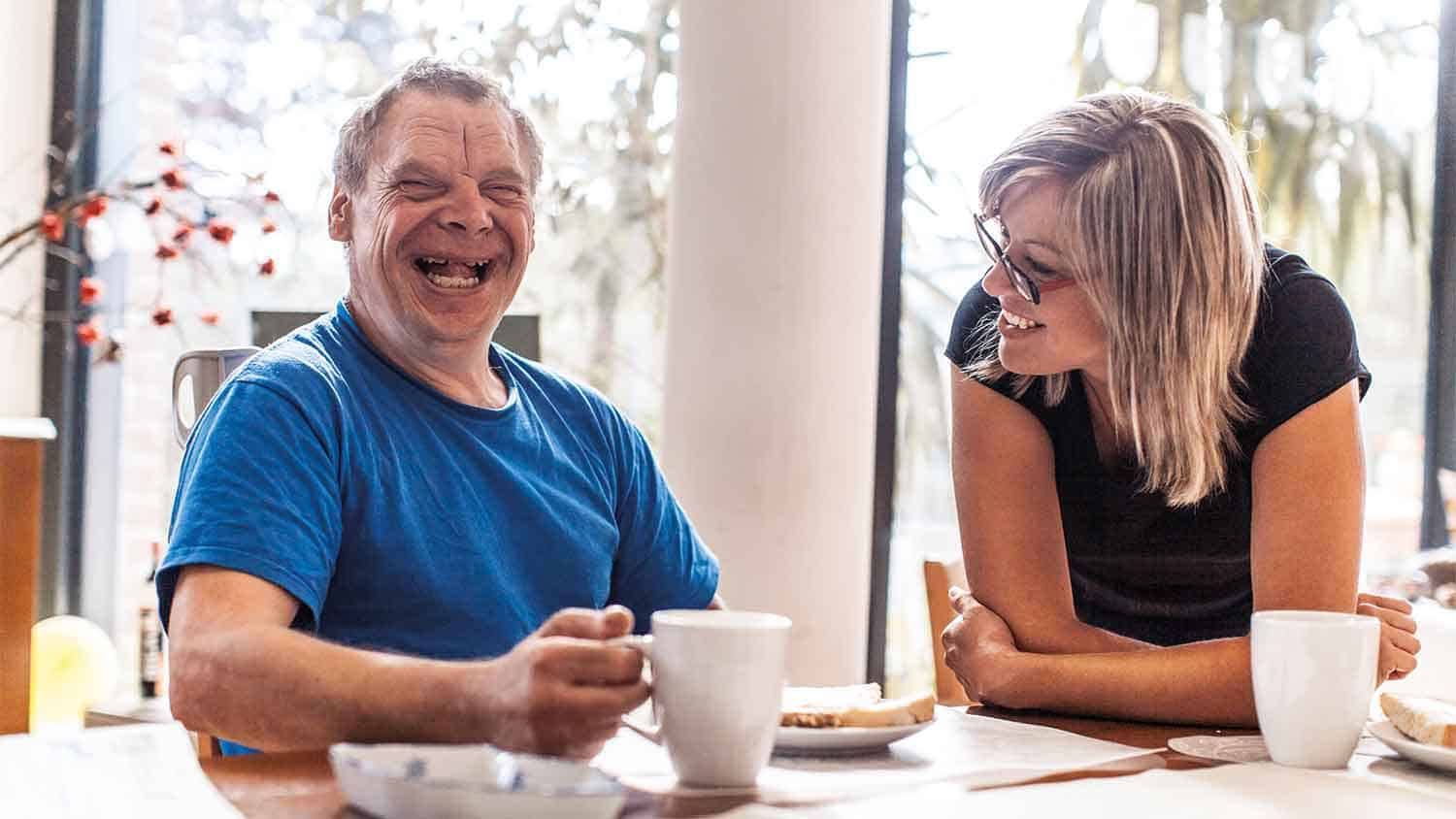 A man with down syndrome enjoying coffee with someone
