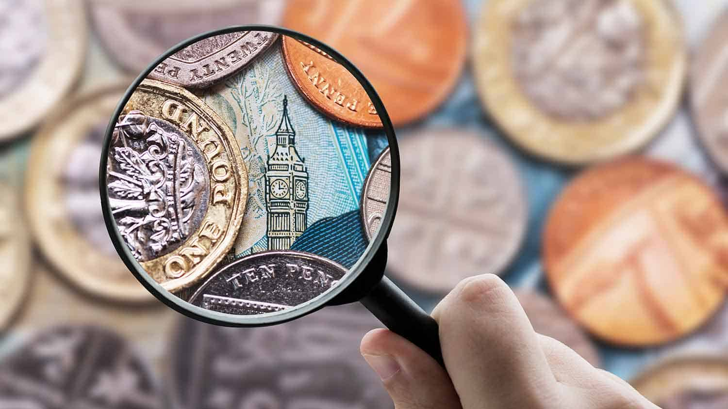Magnifying glass looking closely at a five pound note