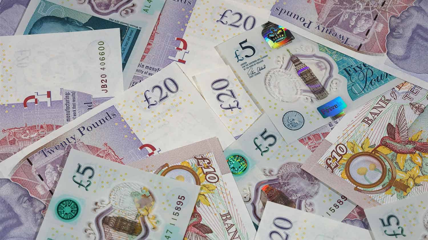Different denominations of £ notes on a table.
