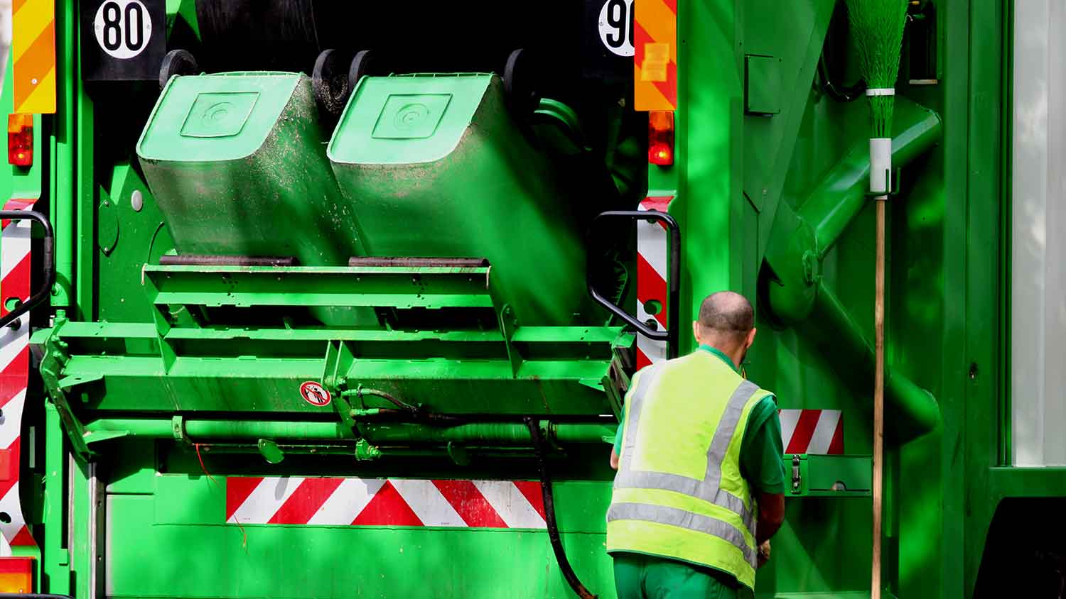 a green bin lorry tipping two bins into the truck